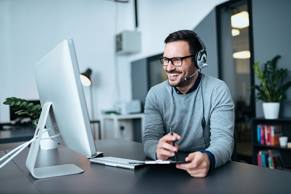 Portrait of a casual smiling businessman using headset when talking to customer